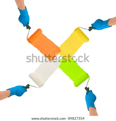Hands with rollers dipped in bright colors paint each other trace on white background - stock photo