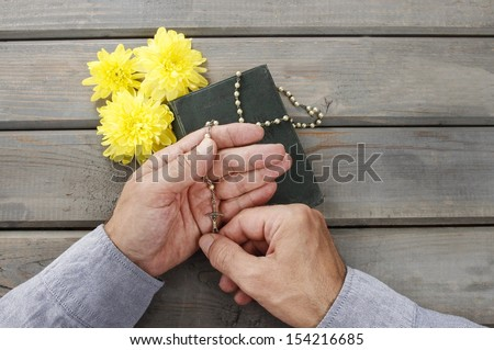 Hands with rosary over old Holy Bible. Wooden background. - stock photo