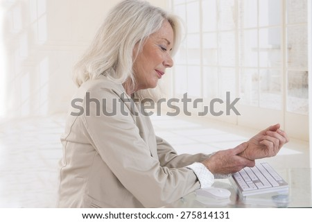 Hands with RSI syndrome over the keyboard of laptop computer - stock photo