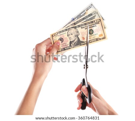 Hands with scissors cutting dollar banknotes, isolated on white - stock photo