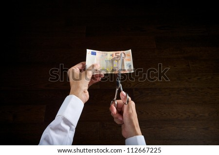 hands with scissors ready to cut a 50 euros banknote - stock photo