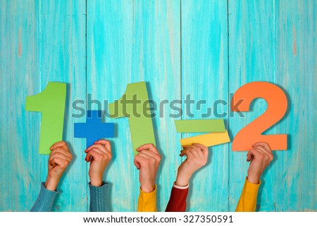 Hands with simple mathematical equation against blue wooden wall