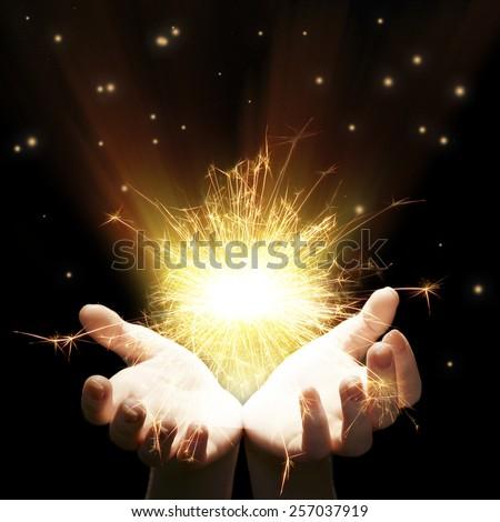 Hands with sparkler light on dark background - stock photo