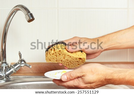 Hands with sponge and dirty saucer over the sink in the kitchen - stock photo
