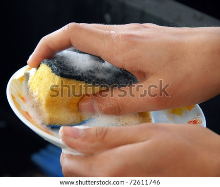 hands with sponge washing dishes in kitchen sink