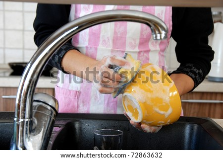 hands with sponge washing dishes in kitchen sink - stock photo