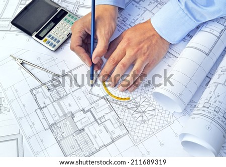 Hands with the tool on a background of project drawings - stock photo