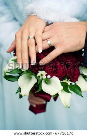 Hands with wedding gold rings and flowers