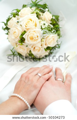 Hands with wedding rings from a newly married couple and bouquet - stock photo
