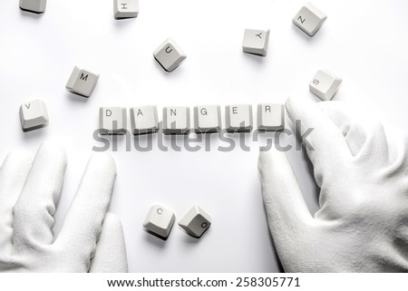 Hands with white gloves typesetting danger with white keys on white background.