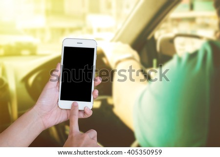 Hands woman are holding touch screen smart phone,tablet on blurred man driving car background.