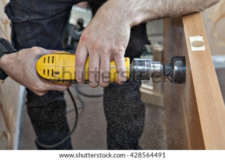Hands woodworker with yellow electric drill, boring large hole of door lock, using hole saw drill bits, sawdust flying around, close-up. - stock photo