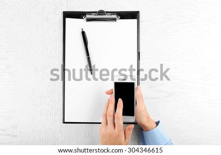 Hands working in the office with documents  and phone on white table
