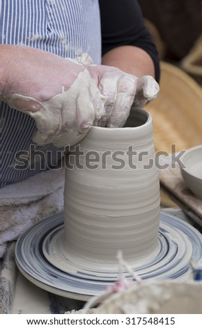Hands working on pottery wheel - stock photo