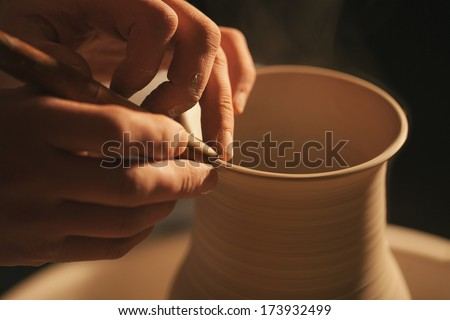 Hands working on pottery wheel ,  retro style toned  - stock photo