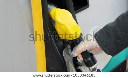 Hands worn by gloves and holding hoses to prevent static electricity during lubrication.