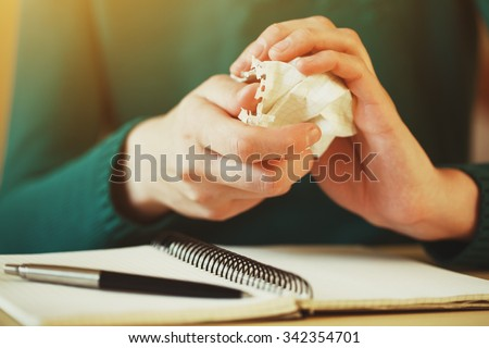 hands wresting the sheet of paper and making paper ball after mistake during writing - stock photo