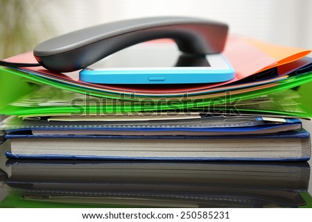 Handset and tablet computer on top of the files and folders. accounting and bookkeeping concept - stock photo