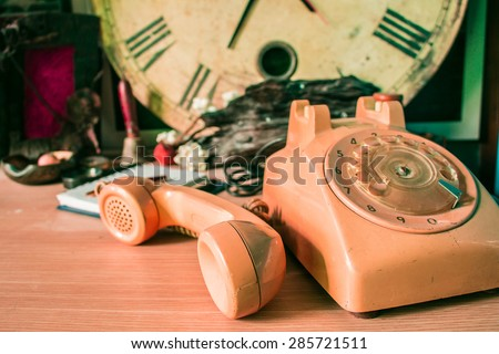 Handset of phone on a wooden table - stock photo