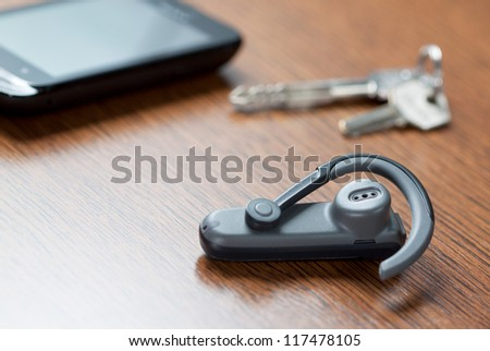 Handsfree with mobile phone and car keys in background - stock photo