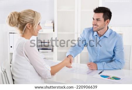 Handshake: Adviser says hello to his female customer. - stock photo