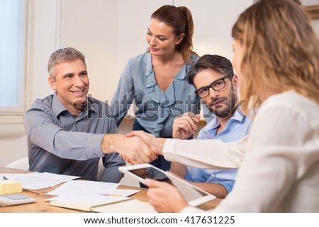 Handshake after a job recruitment meeting. Successful businesspeople shaking hands in front of their colleagues. Mature businessman shaking hands to seal a deal with businesswoman in office.   - stock photo