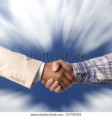 Handshake against the blue sky - stock photo