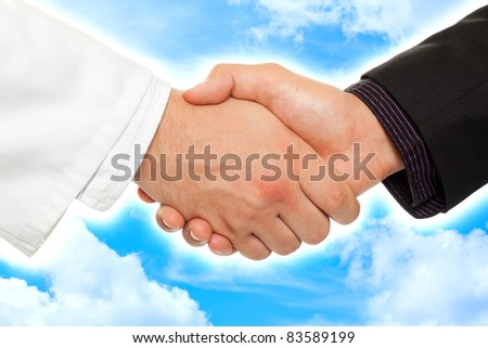 Handshake between a businessman and a doctor, with sky background.