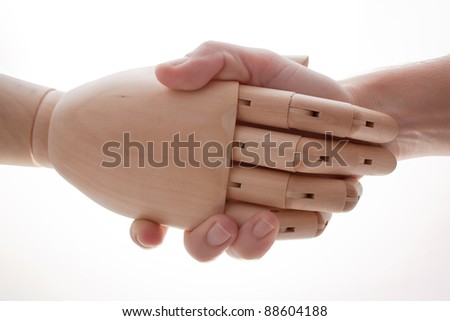 Handshake between a human hand and a wooden hand - stock photo