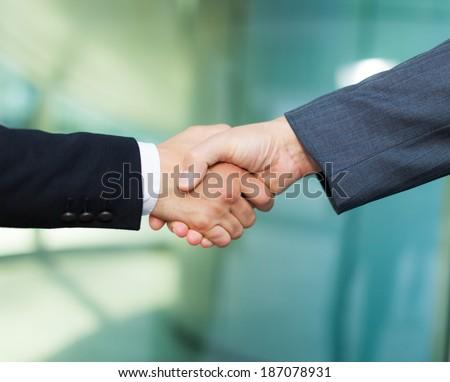 Handshake between business men - stock photo
