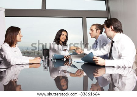 Handshake between businesspeople in a stylish office with harbour in the background - stock photo