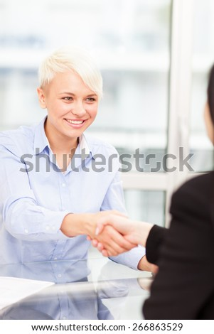 Handshake between businesswomen in the office - stock photo