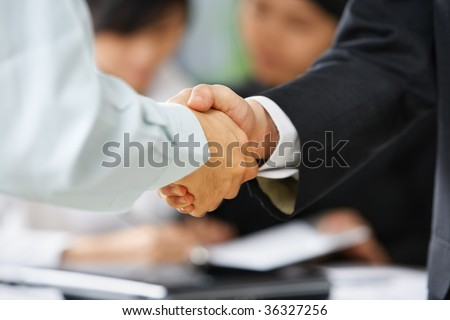 Handshake between employee and boss to illustrate he is being accepted in the team - stock photo