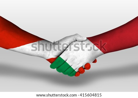 Handshake between italy and austria flags painted on hands, illustration with clipping path. - stock photo