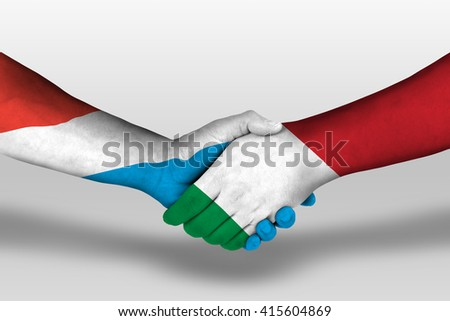Handshake between italy and luxembourg flags painted on hands, illustration with clipping path. - stock photo
