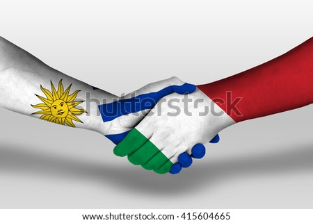 Handshake between italy and uruguay flags painted on hands, illustration with clipping path. - stock photo