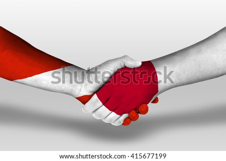 Handshake between japan and austria flags painted on hands, illustration with clipping path.
