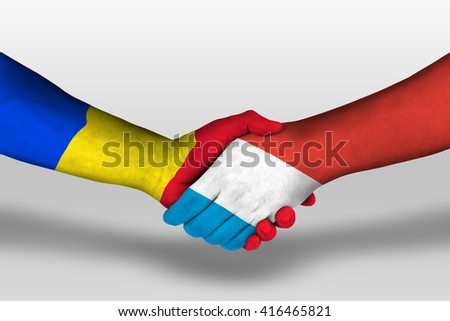 Handshake between luxembourg and romania flags painted on hands, illustration with clipping path.