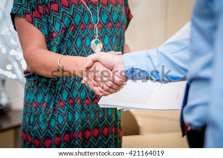 Handshake between man and woman with documents in background - stock photo
