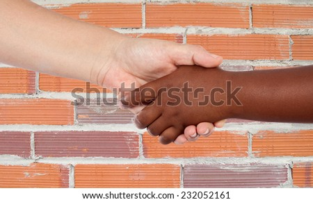 Handshake between races with a brick wall background - stock photo
