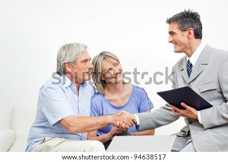 Handshake between senior couple and financial consultant