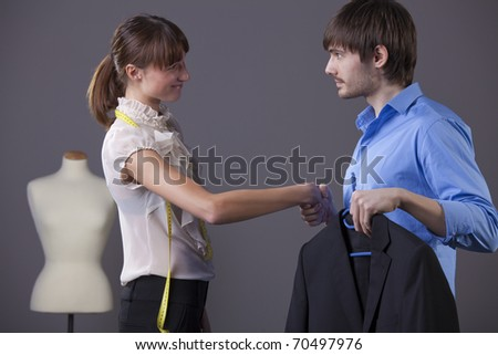 handshake between tailor and customer with business jacket - stock photo