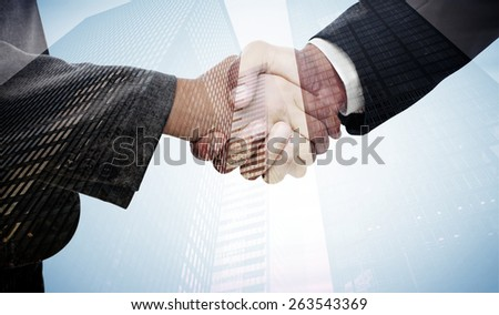 Handshake between two business people against low angle view of skyscrapers - stock photo