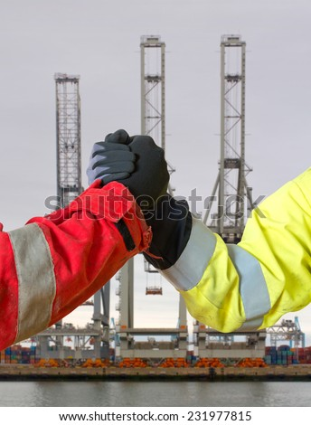 Handshake between two people in work clothing, symbolizing a lucrative deal for in- or export against three harbor cranes - stock photo