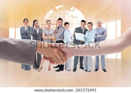 Handshake between two women against shiny planet floating in orange room - stock photo