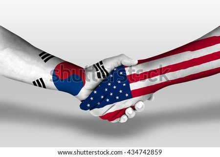 Handshake between united states of america and south korea flags painted on hands, illustration with clipping path.