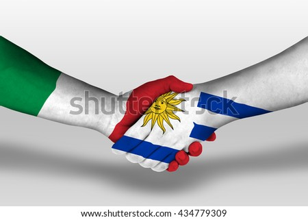 Handshake between uruguay and italy flags painted on hands, illustration with clipping path. - stock photo