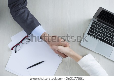 Handshake - business man and business woman hands holding. Top view for top managers - stock photo