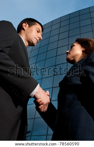 Handshake business man and woman on modern building background - stock photo