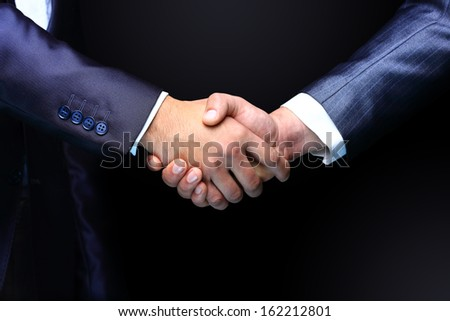 Handshake - Hand holding on black background - stock photo